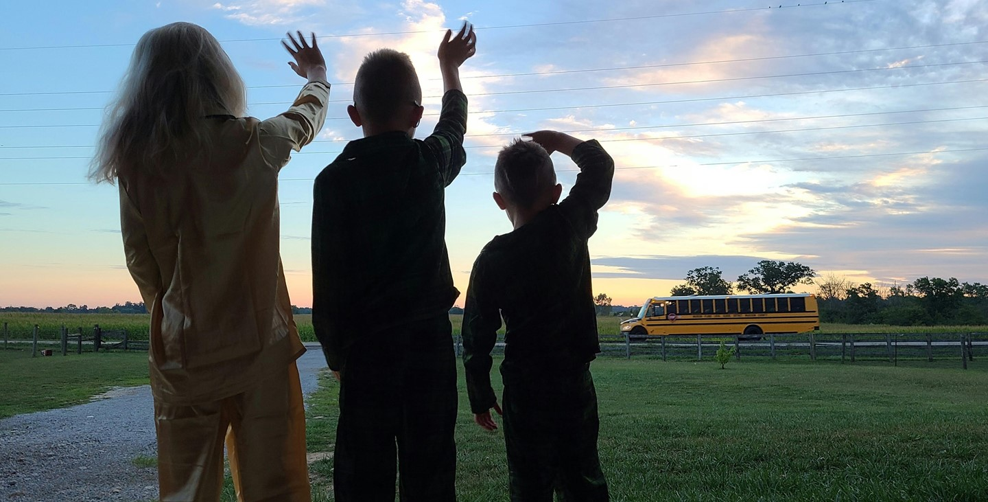 Virtual learning students waving at the school bus going by their house