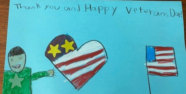 "Crayon drawing of a child, heart, and flag that reads ""Thank you and Happy Veteran's Day!"""