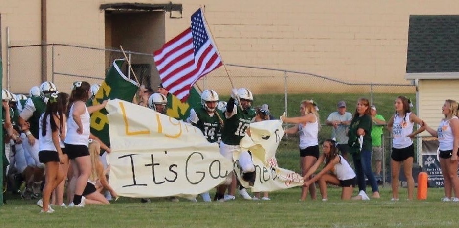 Football player carrying the American flag busting through the banner at the football game