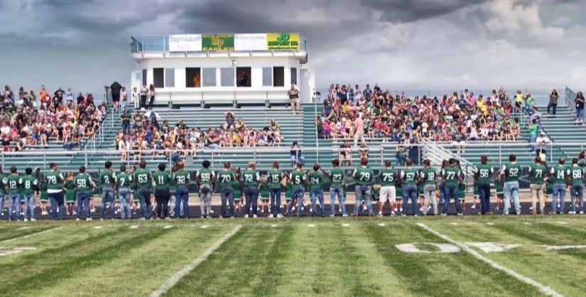 Football team at a Friday night football game, lined up facing the crowd